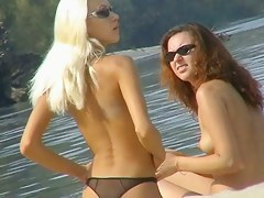 One topless together with one pantieless mollycoddle on beach spy cam