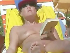 Hot video of a grown-up woman reading a book on a nudist beach