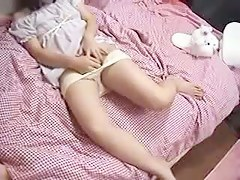 Japanese girl plays with her hairy pussy on her pink bed