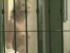 Blonde lady with naked natural boobs in the voyeur thru window clip