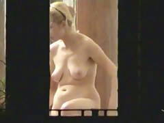 Blonde housewife with huge tits is oiling her body