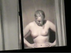 Topless bimbo is kinkily voyeured through the window