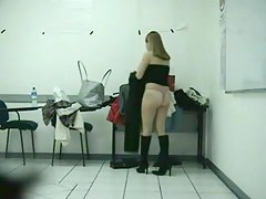 A girl wearing high-heeled boots is changing her skirt in the dressing room