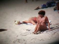 Nudist beach with dressed gentlemen and topless ladies