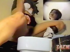 Naughty female is masturbating sitting over toilet bowl